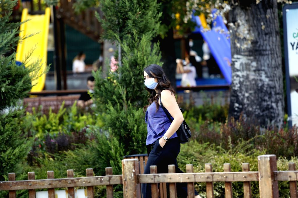 A woman wearing a face mask walks in a park in Ankara, Turkey, on Aug. 28, 2020. Turkey confirmed 1,517 new COVID-19 cases on Friday, raising the total diagnosed ... - Fahrettin Koca