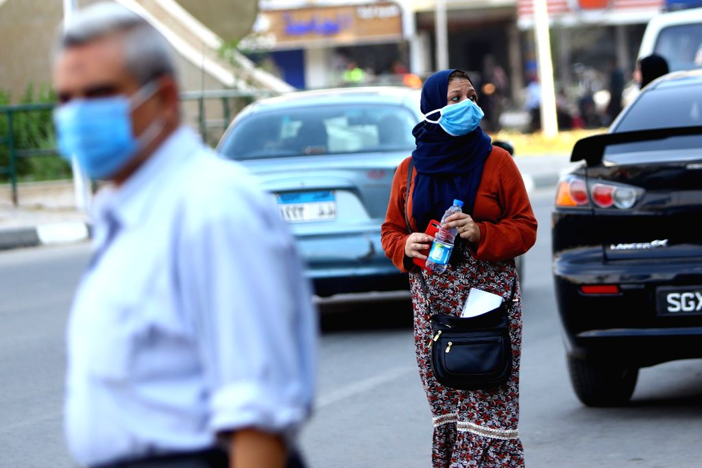 A woman wearing a face mask walks on a street in Cairo, Egypt, on Aug. 12, 2020. Egypt confirmed on Wednesday 129 new COVID-19 infections, bringing the total cases ...