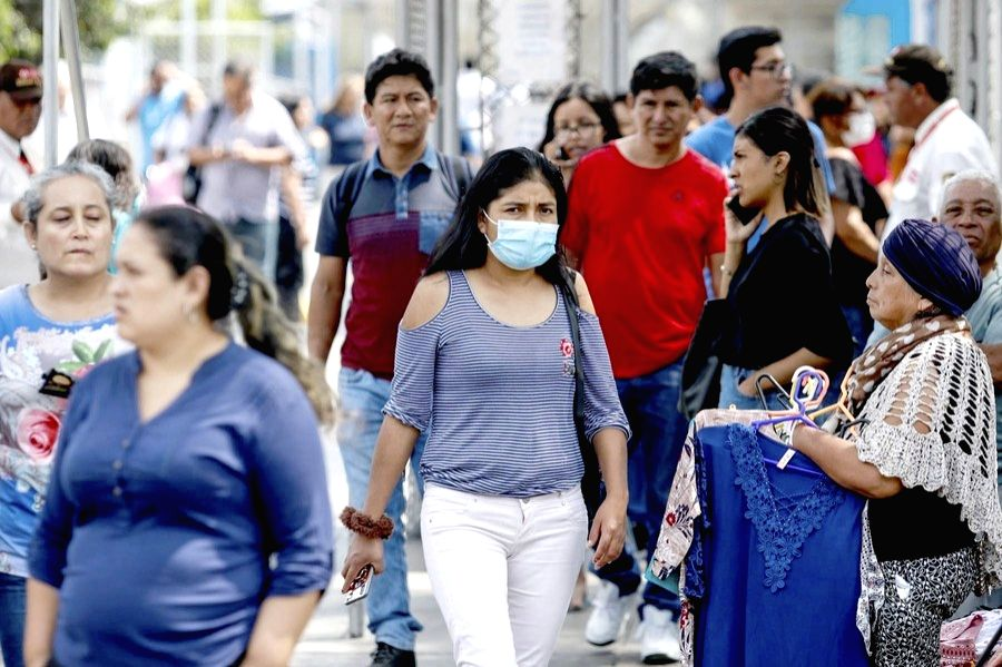 A woman wearing a face mask walks on a street in Lima, Peru, on March 6, 2020.