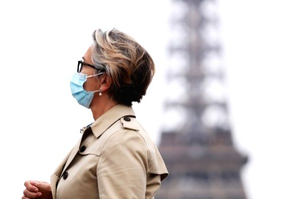 A woman wearing a face mask walks past the Trocadero Place near the Eiffel Tower in Paris, France, Oct. 23, 2020.