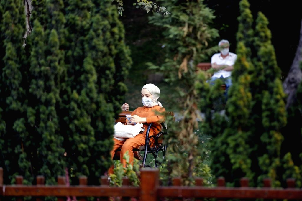 A woman wearing a mask is seen on a bench at a park in Ankara, Turkey, on Sept. 11, 2020. Turkey confirmed 1,671 new COVID-19 cases on Friday, raising the total ...