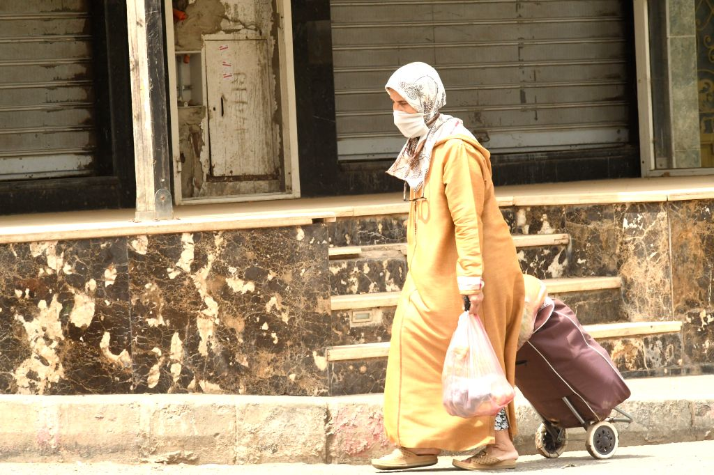 A woman wearing face mask walks on the street in Temara, Morocco, July 30, 2020. Morocco on Thursday reported 1,046 new COVID-19 cases, the biggest single-day ...