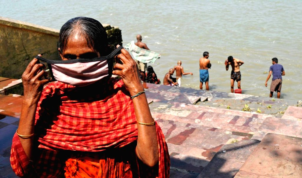 A woman wears a mask after taking a bath in the Ganga river on Day 5 of the 21-day countrywide lockdown imposed to contain the spread of novel coronavirus, in Kolkata on March 29, 2020.