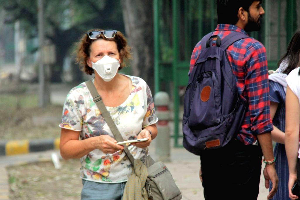 A woman wears mask to protect herself from air pollution as toxic haze continues to engulf the national capital, on Nov 13, 2019. The Delhi air quality index (AQI) is at emergency levels ...