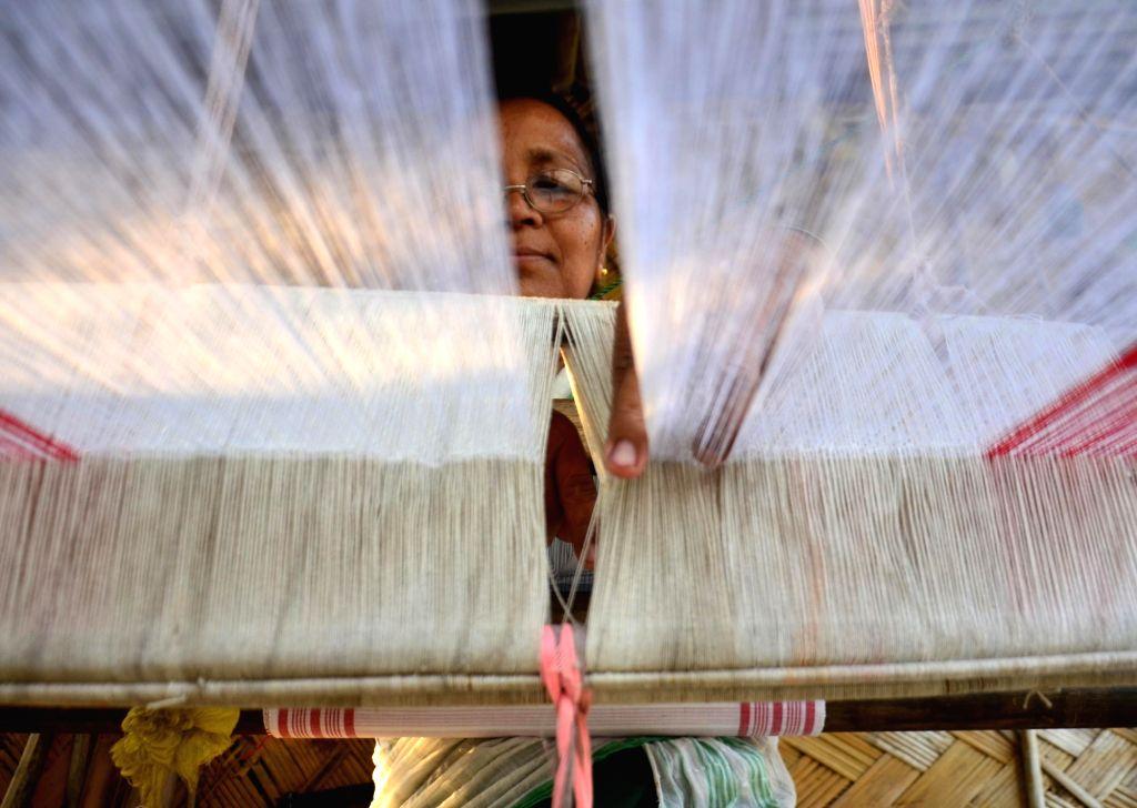 A woman weaves a Gamocha - Assamese handwoven towel, on a handloom ahead of Bohag Bihu celebrations in Assam's Kamrup district on April 4, 2018.