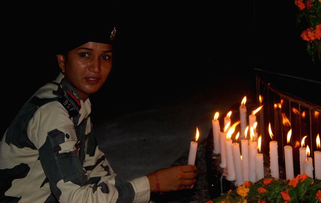 A women constable lighting candle at friendship monument on the eve of India`s Independence Day at Attari/Wahga Indo-Pak border about 35km from Amritsar, on Aug 14, 2015.