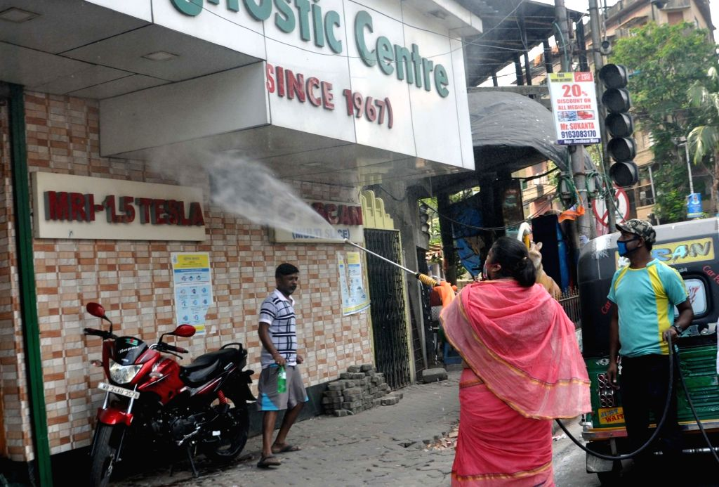 A women heat worker sprays disinfectants on Day 7 of the 21-day nationwide lockdown imposed to contain the coronavirus, in Kolkata on March 31, 2020.