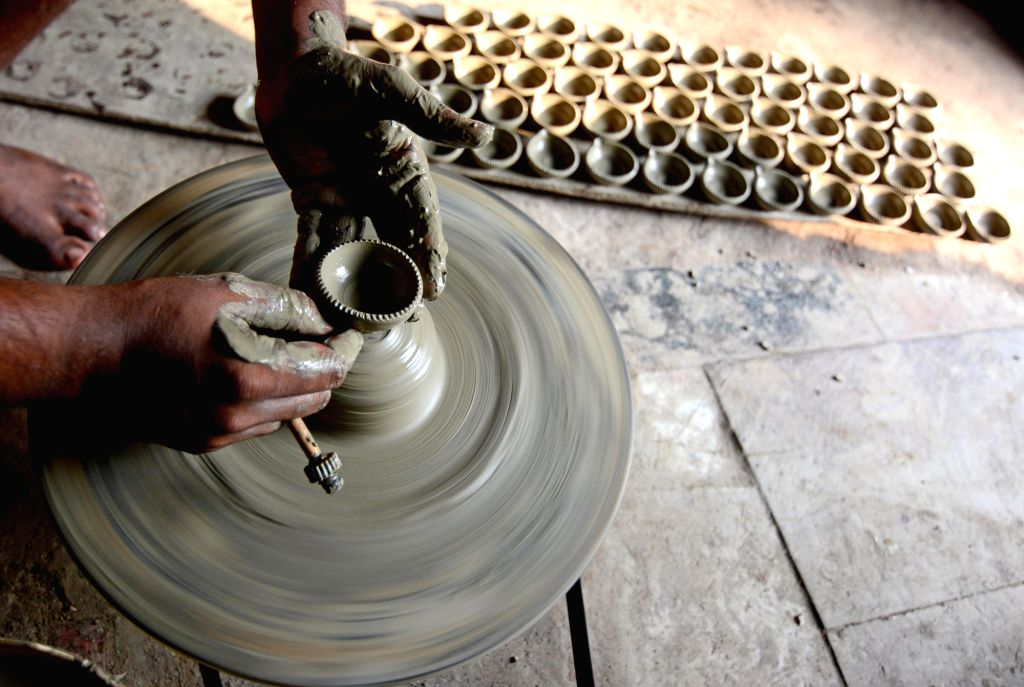 A worker busy preparing earthen lamps at a  workshop ahead of Diwali celebrations, in Kolkata on Oct 18, 2019.