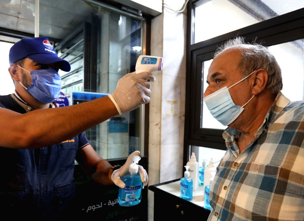A worker checks temperature of a customer at the entrance to a shopping center in Baghdad, Iraq, Aug. 13, 2020. The Iraqi Health Ministry on Thursday recorded 3,841 ...