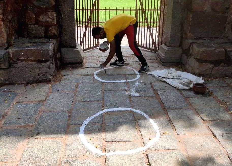 A worker draws circles with a chalk for people to maintain social distance at the entry gates of the Taj Mahal which is likely to reopen from tomorrow, in Agra on July 5, 2020. The Union ...
