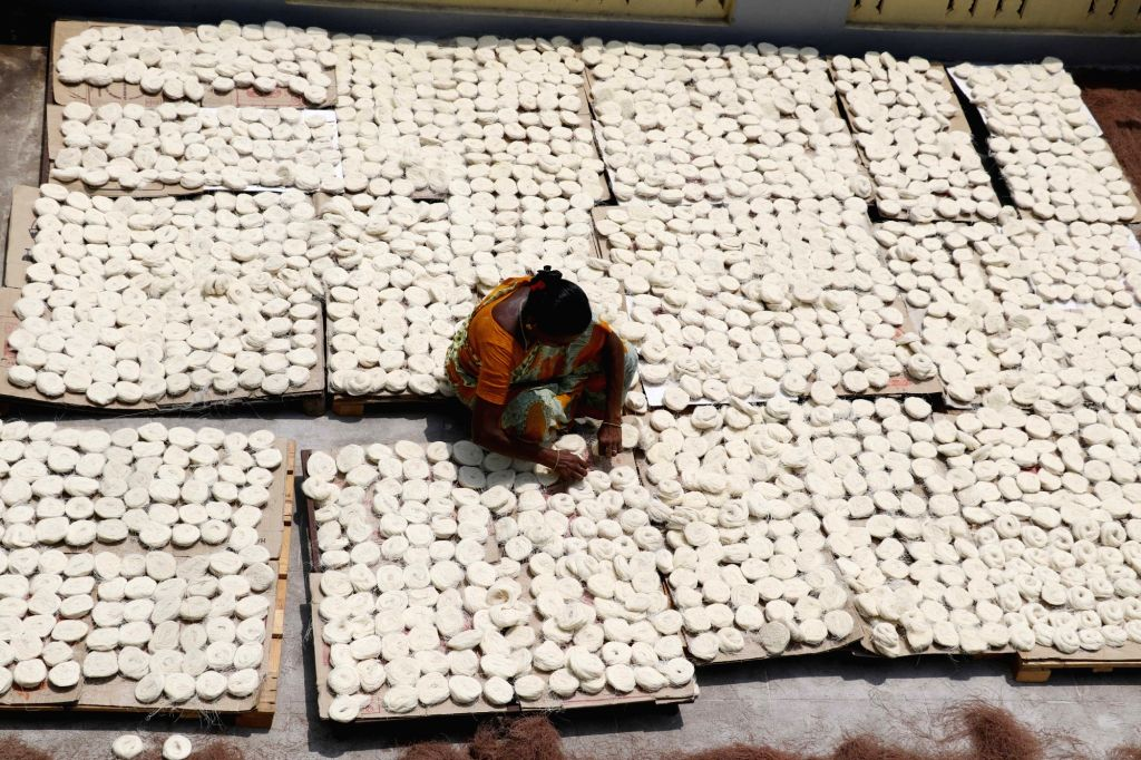 A worker dries vermicelli, used to prepare various sweet dishes consumed during the holy month of Ramadan, at a vermicelli manufacturing unit in Chennai on May 21, 2018.