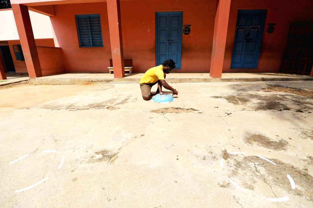 A worker makes draws marks for people to maintain social distancing at a polling station ahead of the Bangalore teacher constituency MLC election, in Bengaluru on Oct 27, 2020.