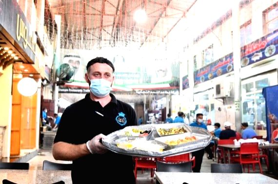 A worker of a Kuwaiti restaurant serves food for customers at the Al-Mubarakiya market in Kuwait City, Kuwait, May 23, 2021.