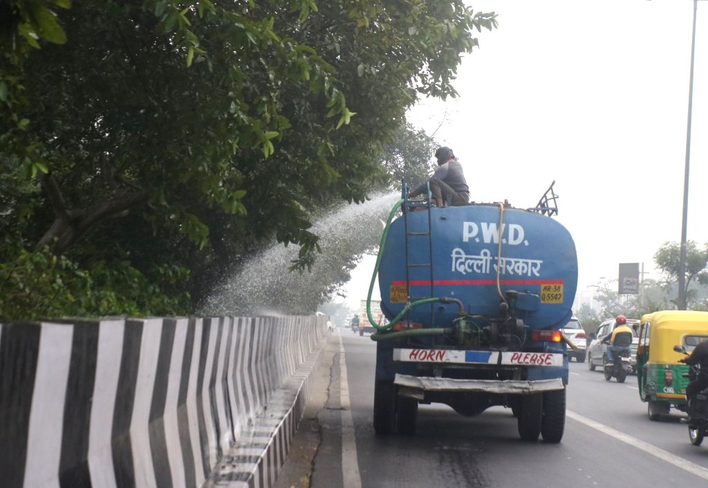 A worker of Public Works Department (PWD) sprinkles water on trees as a measure to reduce air pollution, in New Delhi on Dec 12, 2019.