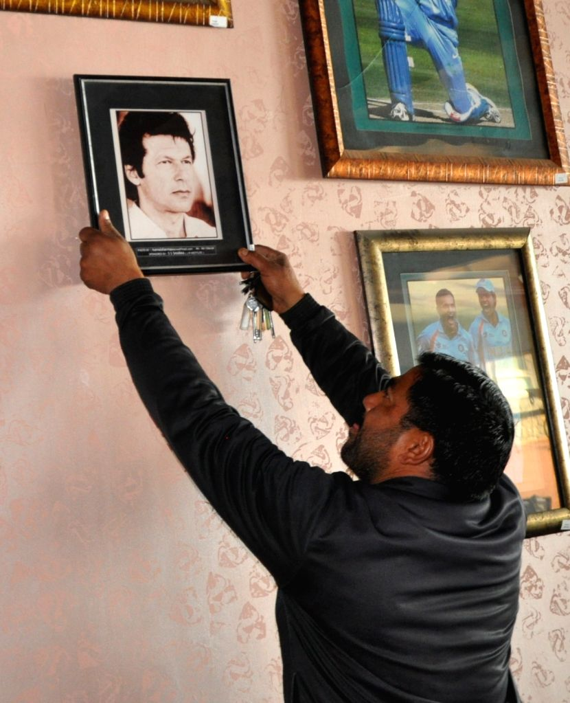 A worker removes a picture of former cricketer and Pakistan Prime Minister Imran Khan from the gallery at Himachal Pradesh Cricket Association (HPCA) Stadium in Dharamsala on Feb 19, 2019. - Imran Khan