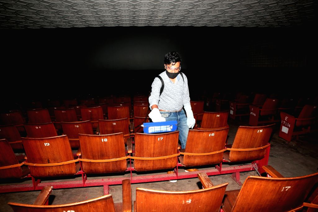 A worker sanitises a cinema hall ahead of its reopening as part of Unlock 5.0 amid COVID-19 pandemic, in Bengaluru on Oct 7, 2020.