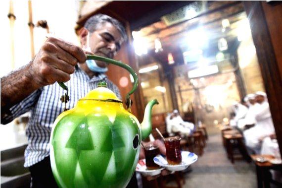 A worker serves tea for customers in a cafe at the Al-Mubarakiya market in Kuwait City, Kuwait, May 23, 2021.