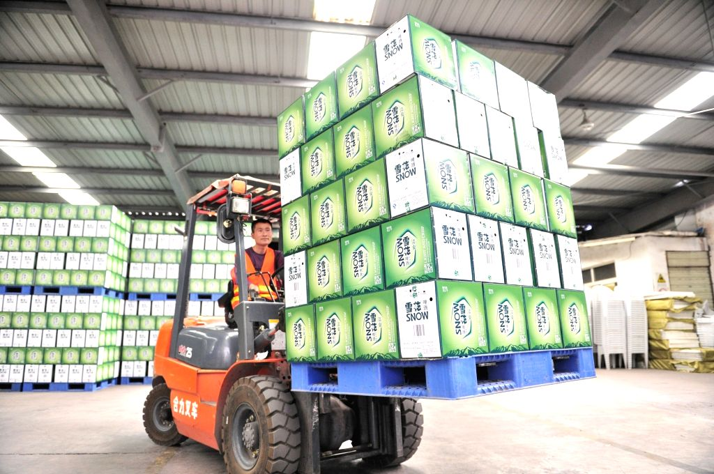 A worker transfers products at a brewery in Chengdu, capital of southwest China's Sichuan Province, August 1, 2015. China's economy grew by 6.9 percent in 2015. ...