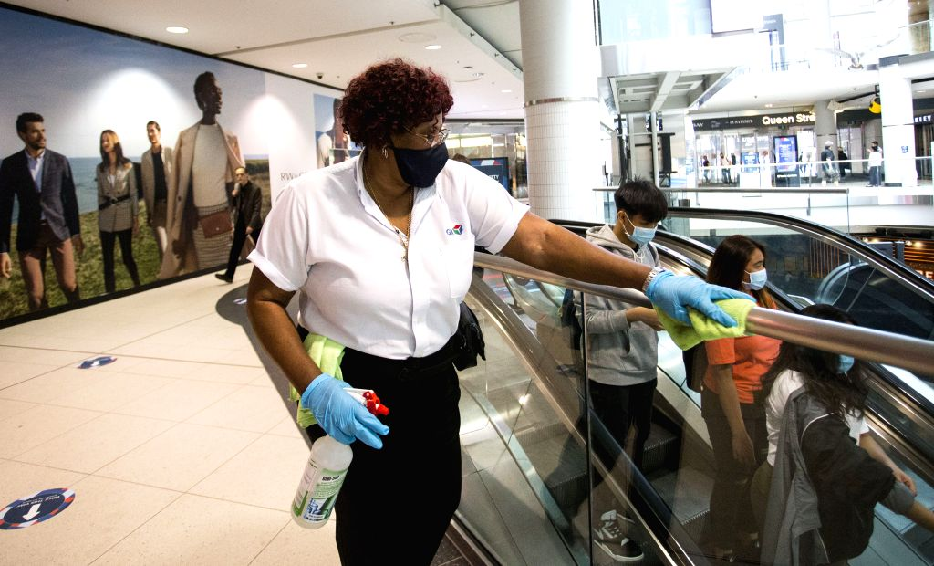 A worker wearing a face mask cleans a handrail at CF Toronto Eaton Center in Toronto, Canada, on June 24, 2020. The City of Toronto moved to the next stage of the ...