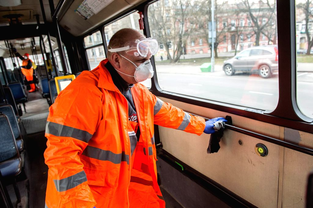 A worker wearing a protective suit disinfects a bus in Vilnius, Lithuania, on March 18, 2020. From March 16 until March 30, Lithuania is under a two-week national ...