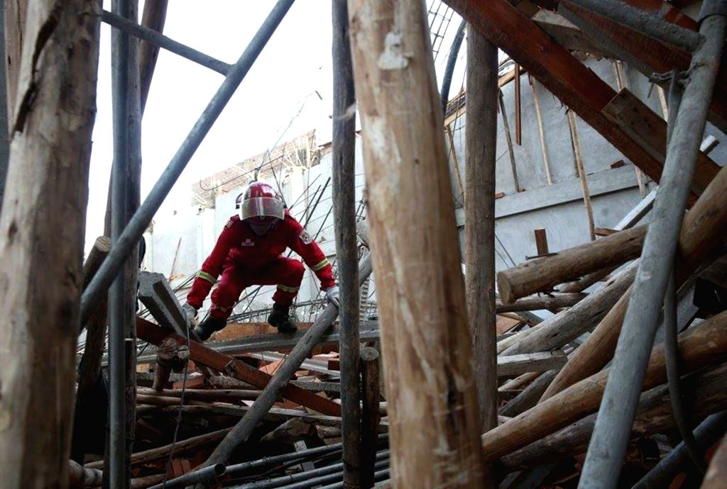 A worker works at the site of a ceiling collapse accident in Lima, Peru, on Aug. 10, 2015. According to local press, 10 people were injured after the collapse of the ...