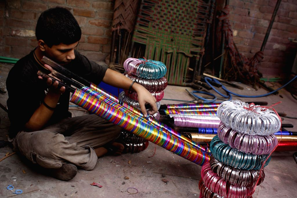 A worker works in a bangle factory ahead of Eid-al-Fitr festival in eastern Pakistan's Lahore, July 13, 2015. Demand of bangle increases before Eid holidays in ...