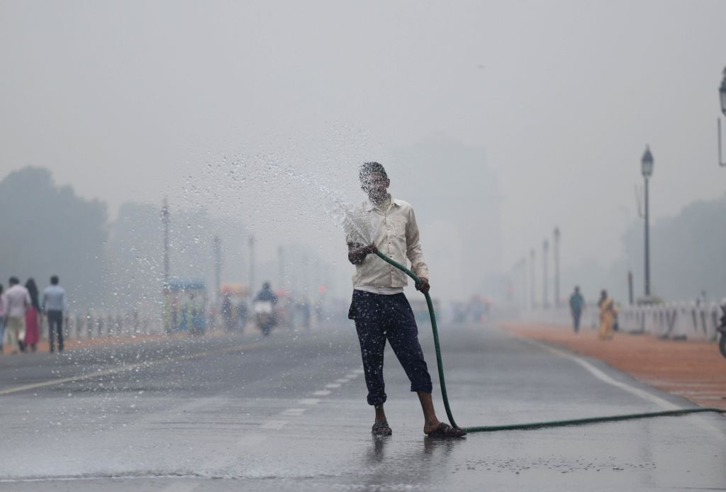 A workers washes a street at Rajpath in New Delhi as a measure to reduce air pollution, on Nov 15, 2019. Delhi has earned the dubious distinction of becoming the most polluted major city ...