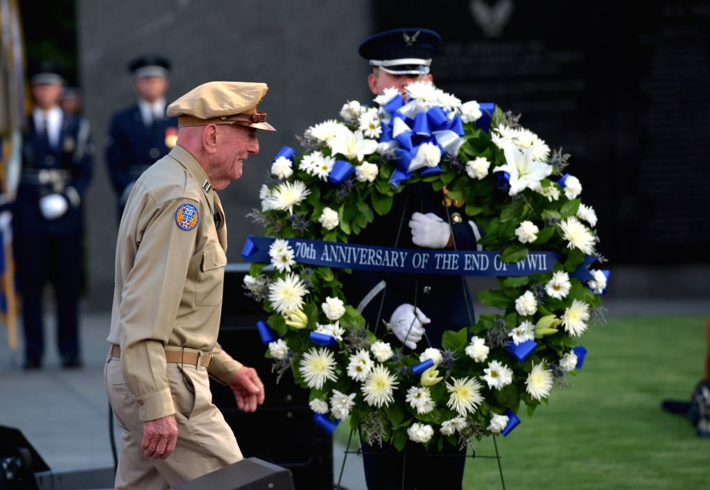 A World War II vetetan walks past a soldier of honor guard during a wreath-laying ceremony marking the 70th anniversary of the end of World War II at the U.S Air ...
