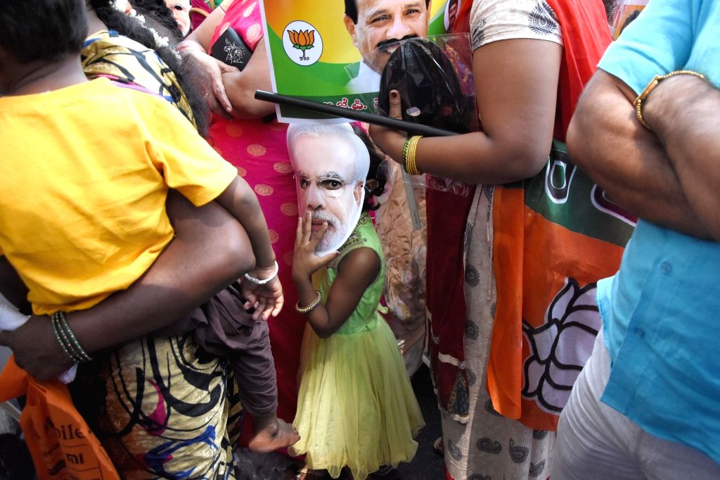 A young BJP supporter wearing a mask of prime Minister Narendra Modi accompanies the party's Lok Sabha candidate from Bengaluru North, D.V. Sadananda Gowda as he heads to file his ... - Narendra Modi