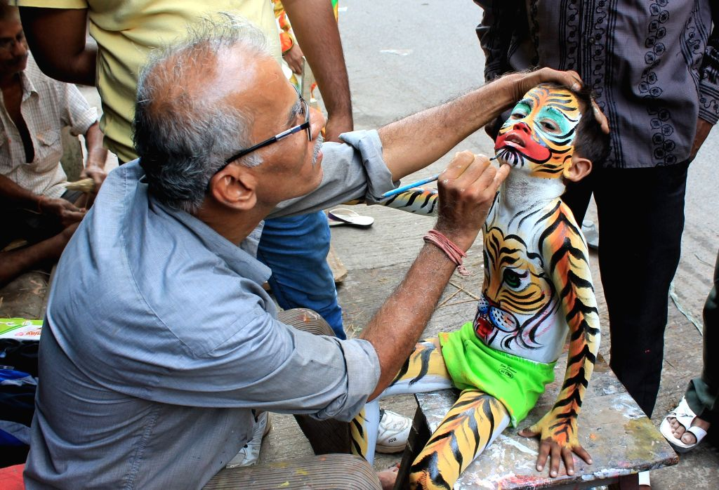 A young boy disguises as tiger ahead of a Muharram procession in Nagpur, on Oct 23, 2015.