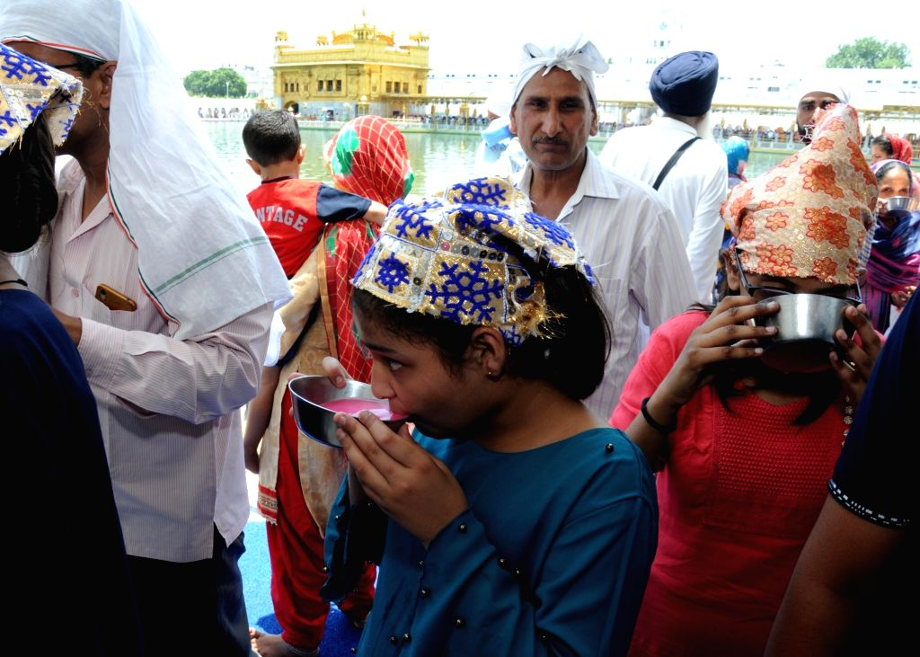 A young devotee drinks sweetened water distributed on the martyrdom day of Guru Arjan Dev at the Golden Temple in Amritsar, on June 7, 2019. - Arjan Dev