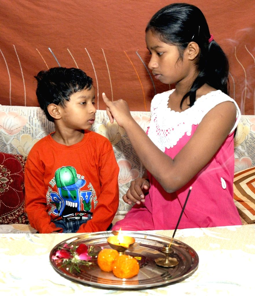 "A young girl applies ""tilak"" - a mark worn on the forehead and other parts of the body for spiritual reasons - on the  forehead of her brother on ""Bhai Dooj"" in New ..."