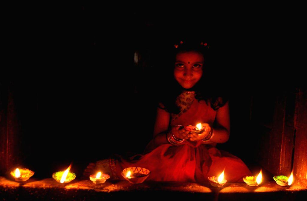 A young girl arranges lit earthen lamps ahead of Diwali in Kolkata on Nov 5, 2018.