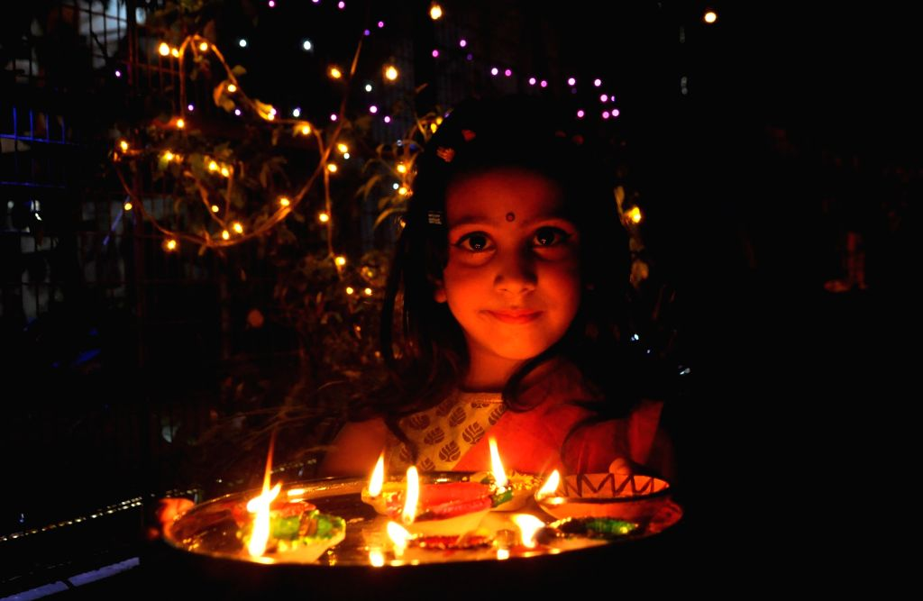 A young girl carries lit earthen lamps ahead of Diwali in Kolkata on Nov 5, 2018.