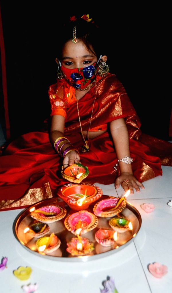 A young girl lighting up earthen lamps at her residence during Diwali celebrations, in Kolkata on Nov 14, 2020.
