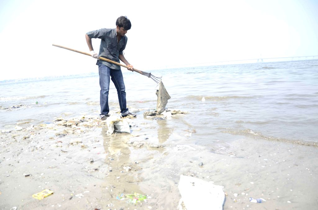 A youth cleans up Dadar sea beach in Mumbai, as Prime Minister Narendra Modi launched Swachh Bharat Abhiyan - a nationwide campaign that aims to clean up India in five years - on Oct. 2, 2014. (Photo: Sandeep Mahankal/IANS) - Narendra Modi