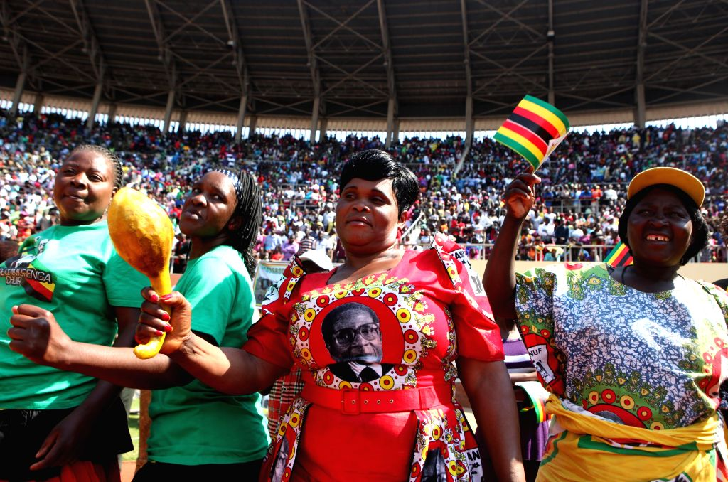 A Zimbabwean woman wearing T-shirt with the photo of President Robert Mugabe is seen dancing with other celebrators at the National Sports Stadium in Harare, ...
