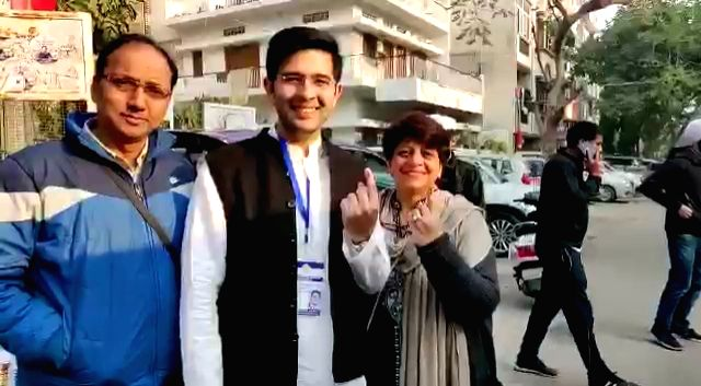 Aam Aadmi Party (AAP) candidate from Rajinder Nagar, Raghav Chadha accompanied by his his parents, show his inked finger after casting his votes for the Delhi Assembly elections 2020, on ...