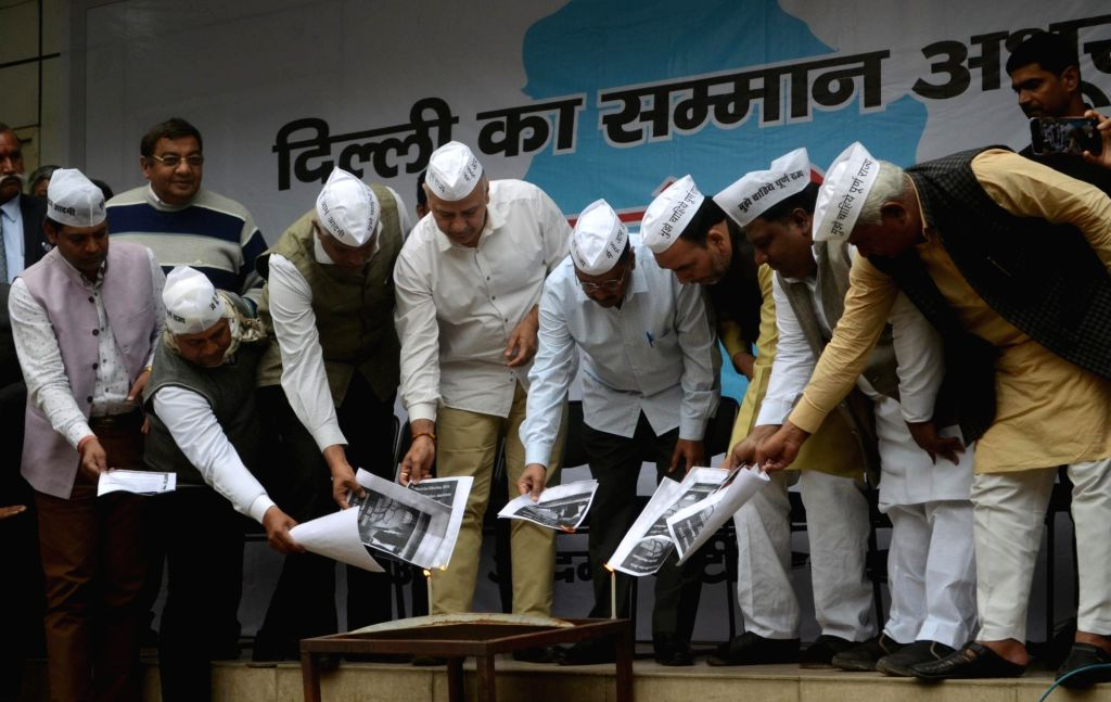 Aam Aadmi Party (AAP) workers led by Delhi Chief Minister and party leader Arvind Kejriwal, Deputy Chief Minister and party leader Manish Sisodia burns BJP's manifesto during a protest in ... - Arvind Kejriwal