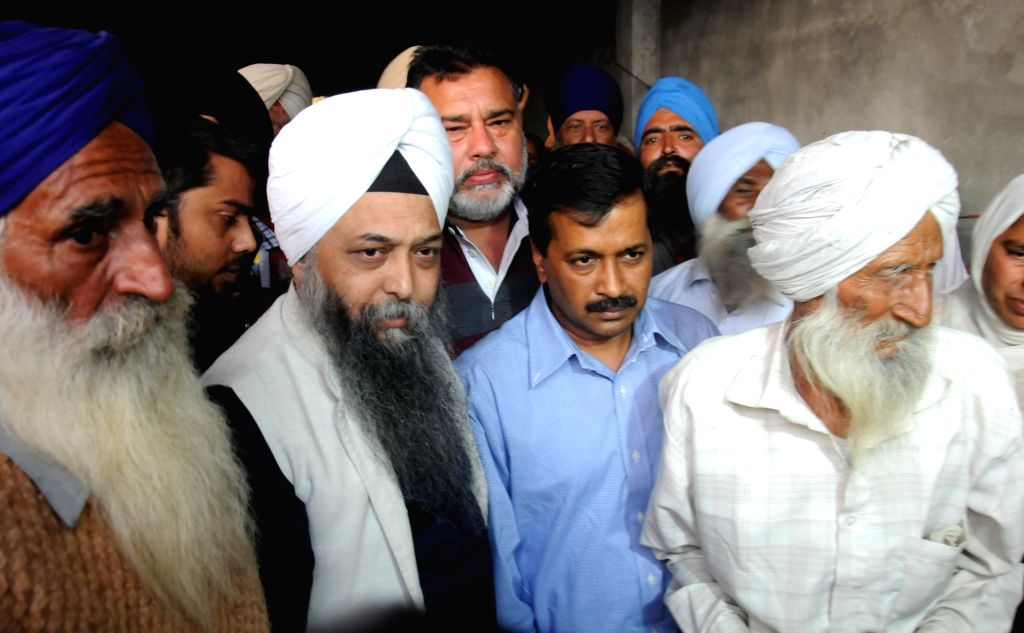 AAP national convener and Delhi Chief minister Arvind Kejriwal meets family members of Ravinder Singh, a farmer of Majjupura village near Fatehgarh Churian who had committed suicide as he ... - Arvind Kejriwal and Ravinder Singh