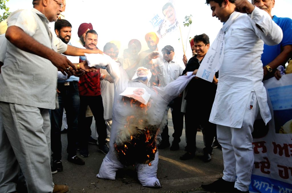 AAP workers burn the effigy of Prime Minister Narendra Modi as they stage a demonstration against rising fuel prices, in Amritsar on Sept 15, 2018. - Narendra Modi