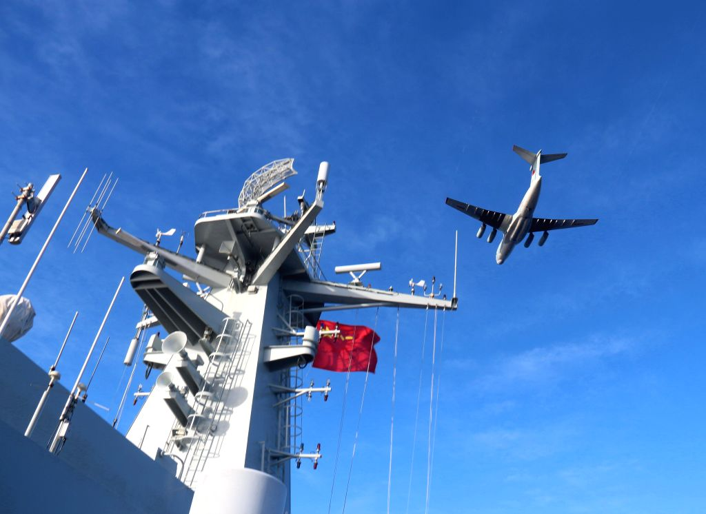 A Chinese Ilyushin IL-76 plane flies over Chinese Navy's amphibious landing vessel Jinggangshan during a joint search mission for the missing Malaysia .