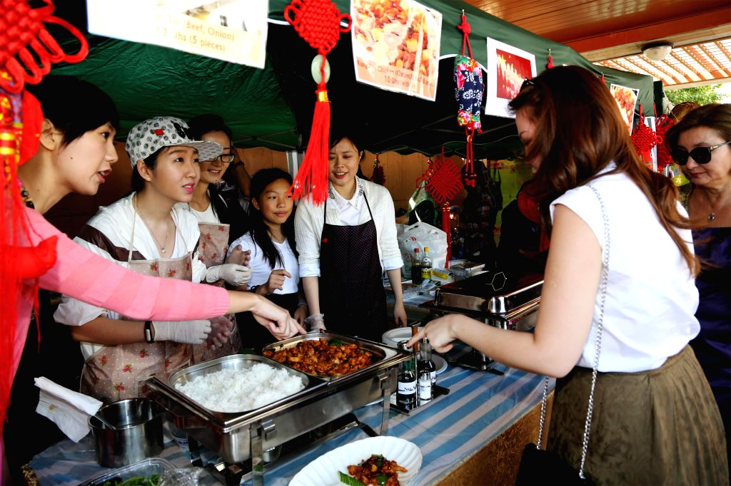Visitors try Kung Pao Chicken, a kind of well-known Chinese dish, during an Asian food festival and charity bazaar at the Embassy of India in Abu Dhabi, Feb. 7, ...