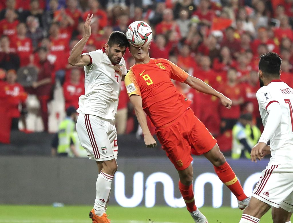ABU DHABI, Jan. 25, 2019 - Xiao Zhi (C) of China competes for a header with Milad Mohammadi (L) of Iran during the 2019 AFC Asian Cup quarterfinal match between China and Iran in Abu Dhabi, the ...