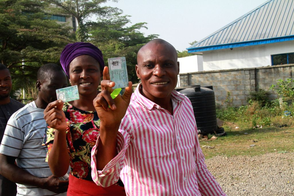 ABUJA, Feb. 23, 2019 - Voters present their Permanent Voter's Cards (PVC) at a polling station during the presidential and National Assembly Elections in Abuja, capital of Nigeria, Feb. 23, 2019. ...