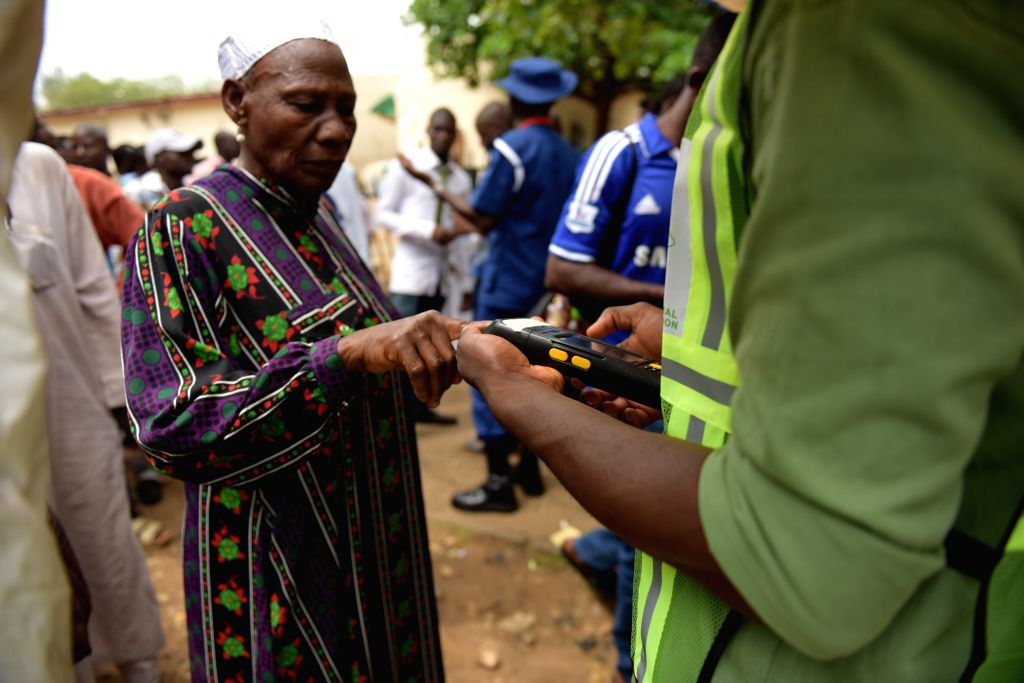 An old female is checked for her identity before the vote at a polling station in Abujia, Nigeria, March 28, 2015. Polling stations across Nigeria opened on ...