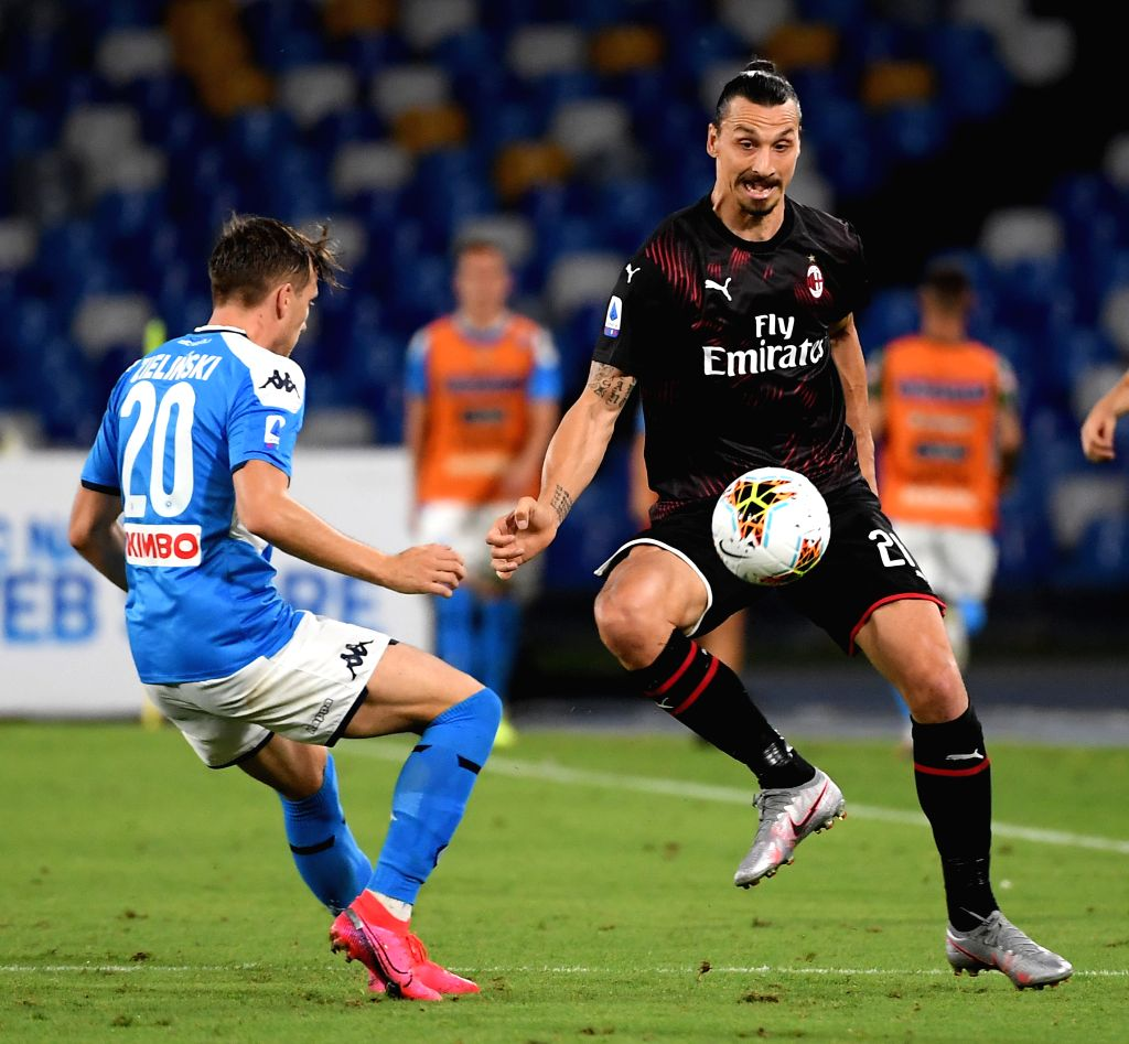 AC Milan's Zlatan Ibrahimovic (R) vies with Napoli's Piotr Zielinski during a Serie A football match between Napoli and AC Milan in Naples, Italy, July 12, 2020.