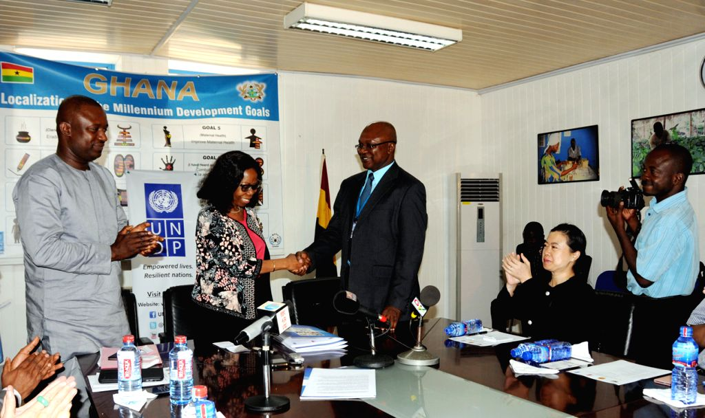 Resident Representative of the UNDP (United Nations Development Program ) Gita Welch (2nd L) shakes hands with Ghana's Executive Secretary of the Energy Commission ...