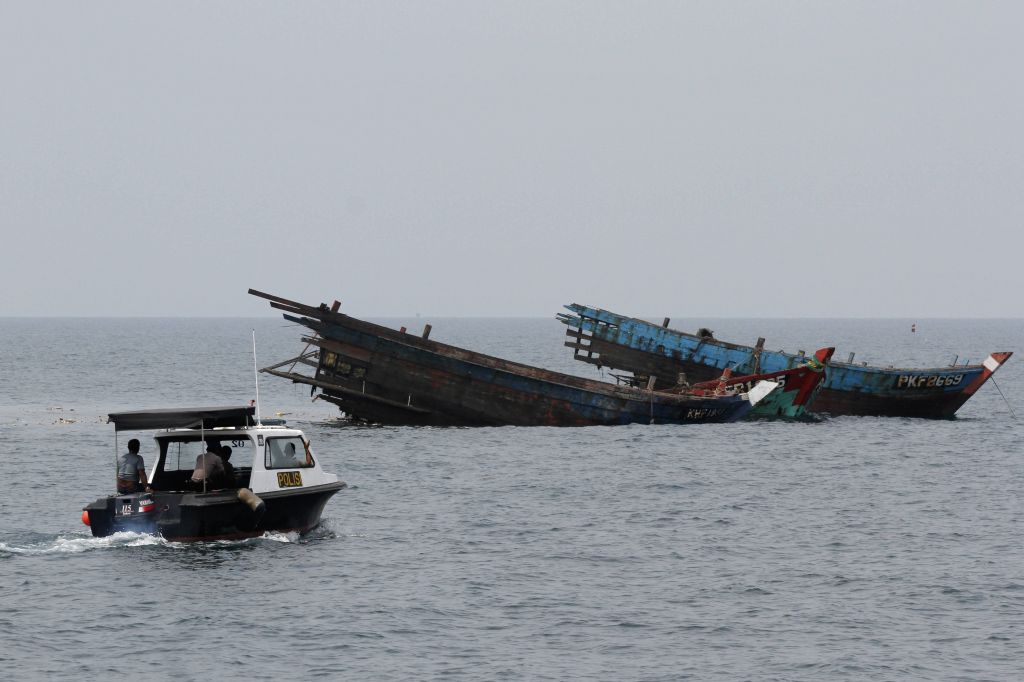 ACEH, April 5, 2016 - Indonesian police officers check the debris of destroyed vessels from Malaysia off the coast of Kuala Langsa in Aceh, Indonesia. April 5, 2016. Indonesian authorities sank 23 ...