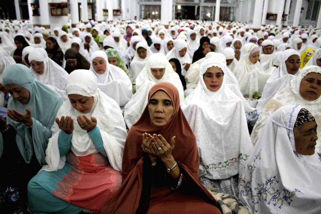Indonesian Muslim women participate in mass praying during 10-year commemoration of Tsunami at Baiturrahman great mosque in Banda Aceh, Indonesia, Dec. 25, 2014. ...